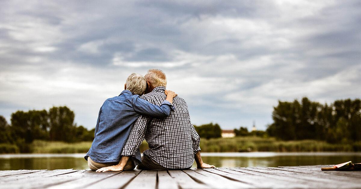 couple enlacé de dos, assis sur un quai devant un lac