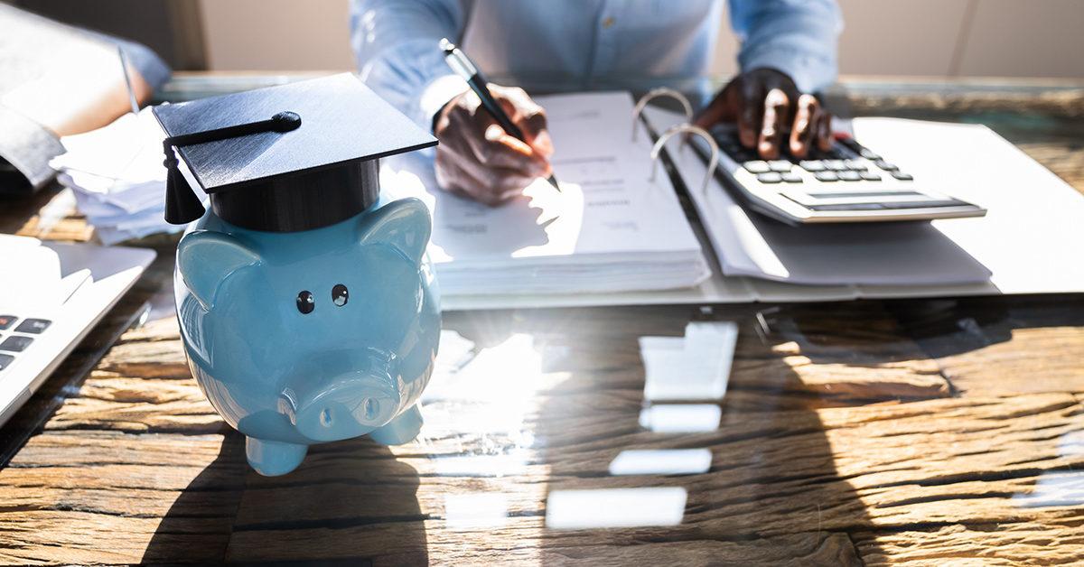 tirelire en forme de cochon bleu, portant un chapeau de finissant scolaire