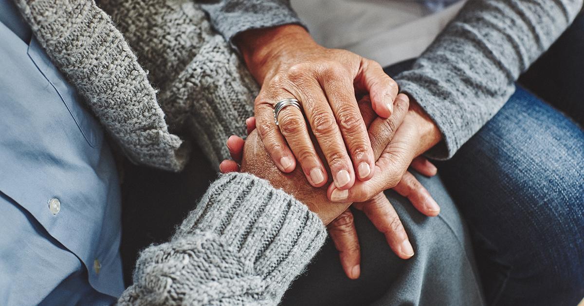 personnes tenant la main de l'autre entre ses deux mains