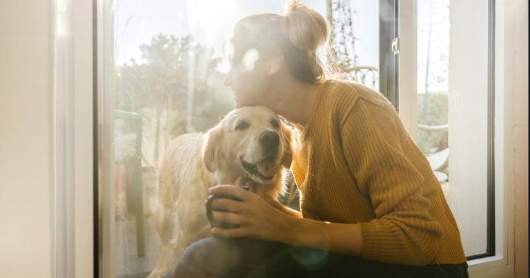 jeune femme blonde qui flatte un chien Golden