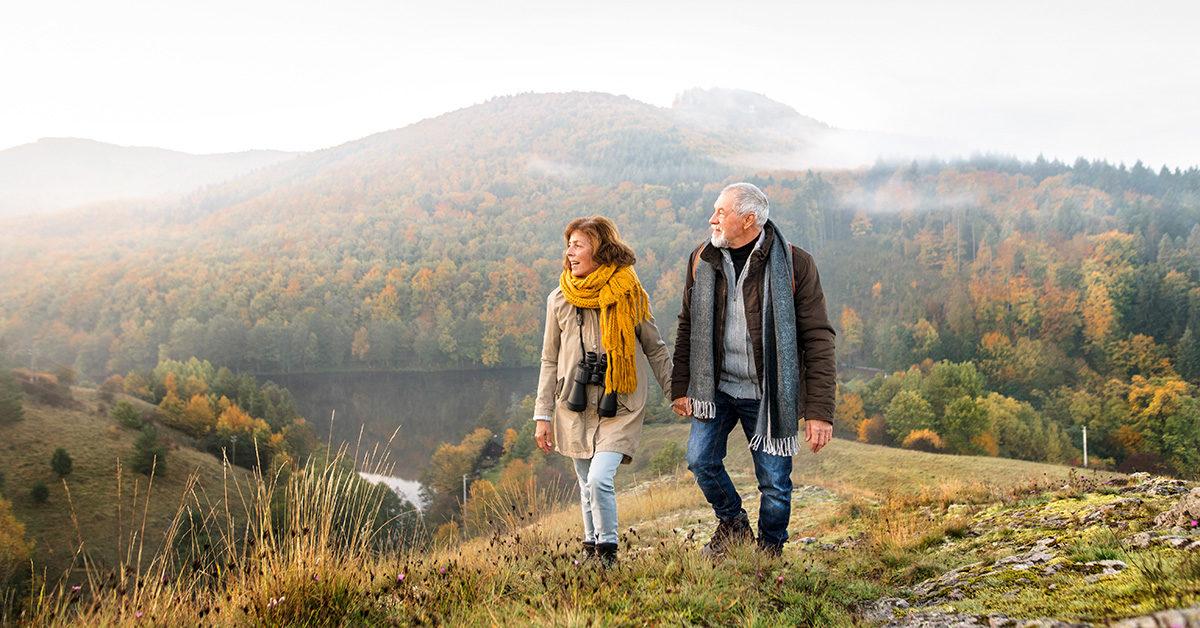 couple sénior marchant dans un magnificque paysage montagneux
