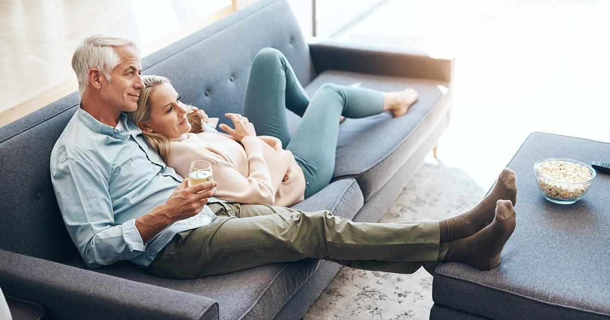 couple homme femme séniors attitude sereine, bien-être, enlacé sur un sofas,