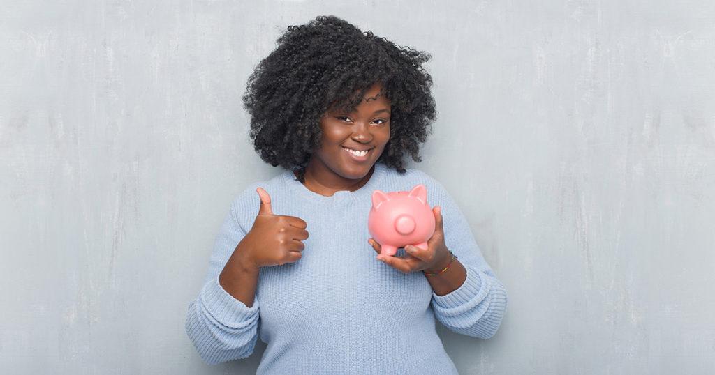 Jeune femme afro-américaine souriante tenant une tirelire de la main droite et pouce en l'air en signe de OK de la main gauche