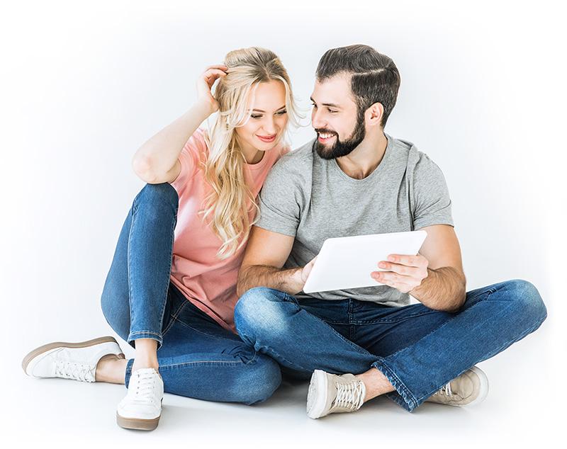 couple femme blonde homme cheveux et barbe brune tenant une tablette d'ordinateur et se souriant