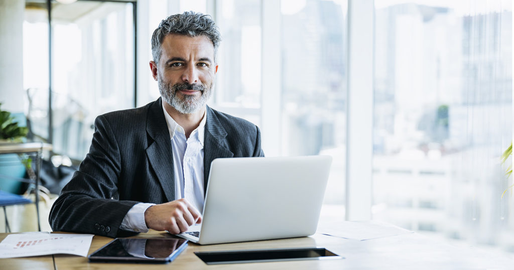 homme d'affaire (syndics) cheveux poivre et sel dans un bureau devant son ordinateur